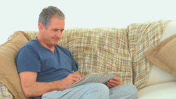 Retired man doing cross words Stock Video Footage