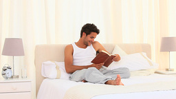 Man in pyjamas reading a book Footage