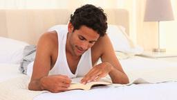 Man in pyjamas reading a book Footage
