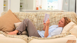 Relaxed woman elongated on her sofa Footage