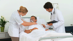 Doctors examining an unconscious man Stock Video Footage