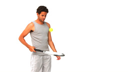 Darkhaired man playing with a racket and tennis ball Footage