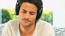 Handsome dark haired man listening to music Stock Video Footage
