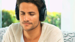 Handsome dark haired man listening to music Footage