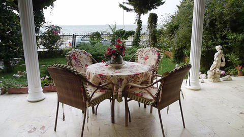 Table on porch overlooking garden and sea - Home -... Stock Video Footage