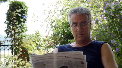 Old retired man reading newspaper Stock Video Footage