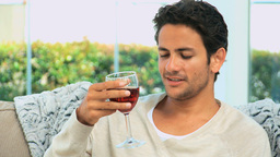 Handsome man savouring a glass of red wine Footage