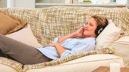Curly blonde woman listening to music Footage
