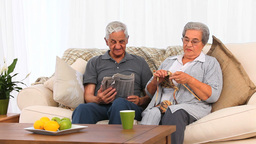 Woman knitting while her husband is reading Stock Video Footage