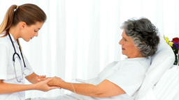 Nurse putting a drip on the arm of her patient Stock Video Footage