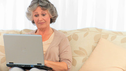 Radiant retired woman looking at her laptop Footage