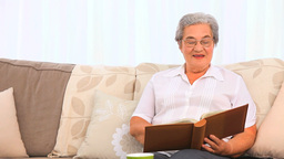 Retired woman looking at her photo album Footage