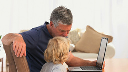 Grandfather with his grandson looking at their laptop Footage