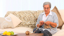 Woman knitting on her sofa Footage