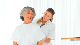 Nurse taking the heartbeat of her mature patient Stock Video Footage