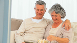 Mature couple eating popcorn in front of the tv Footage