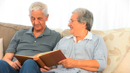 Couple looking at their photo album Stock Video Footage