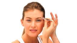 Woman tweezing her eyebrows Stock Video Footage