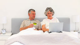 Couple buying something on the net in the bed Footage