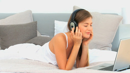 Lovely woman listening to music in her bed Footage