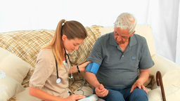 Nurse taking the blood pressure of her male patien Stock Video Footage