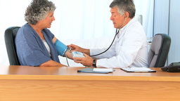 Doctor taking the blood pressure of his retired pa Footage