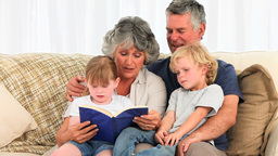 Grandsparents reading a book to their grandchildre Footage