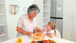 Attentive Grandmother cooking with her granddaughter Footage