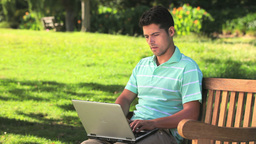 Darkhaired man using laptop outdoors Footage