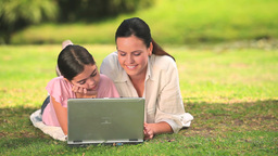 Woman and daughter using a laptop outdoors Footage
