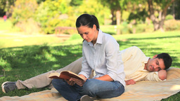 Woman reading a book in a park Footage