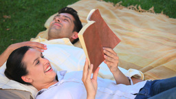 Couple relaxing reading a book outdoors Stock Video Footage