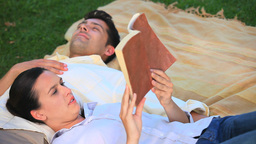 Couple relaxing reading a book outdoors Footage