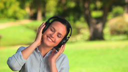 Young woman listening to music outdoors Footage
