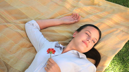 Woman lying outdoors holding a flower Stock Video Footage