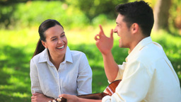 Laughing couple outdoors with guitar Stock Video Footage