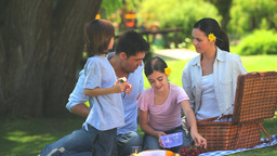Happy family eating fruit outdoors Footage