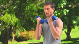 Handsome man doing exercises with dumbbells Footage