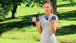 Woman exercising with dumbbells outdoors Stock Video Footage