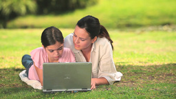 Mother and daughter using a laptop outdoors Footage
