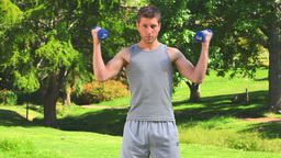 Man using blue dumbbells outdoors Stock Video Footage