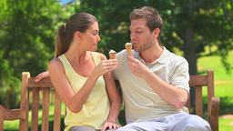 Lovers eating ice creams on a bench Footage