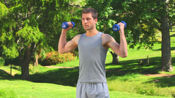 Handsome man using dumbbells outdoors Footage