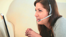 Young woman phoning using laptop and headset Footage