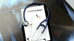 Stethoscope, pills, syringe, and notepad turning Footage