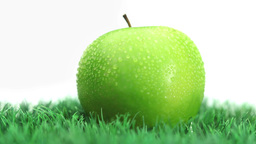 Green apple on grass rotating Stock Video Footage