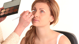 Young woman having her eyes made up by a makeup ar Stock Video Footage