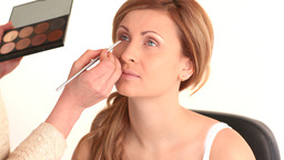 Young woman having her eyes made up by a makeup ar Footage