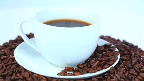Cup of coffee surrounded by coffee beans turning Footage