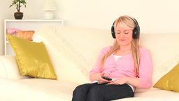 Blondhaired woman listening to music with headphones Footage
